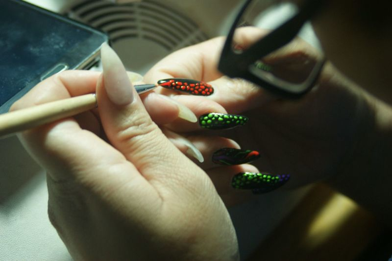 Cropped image of woman hands painting fingernails