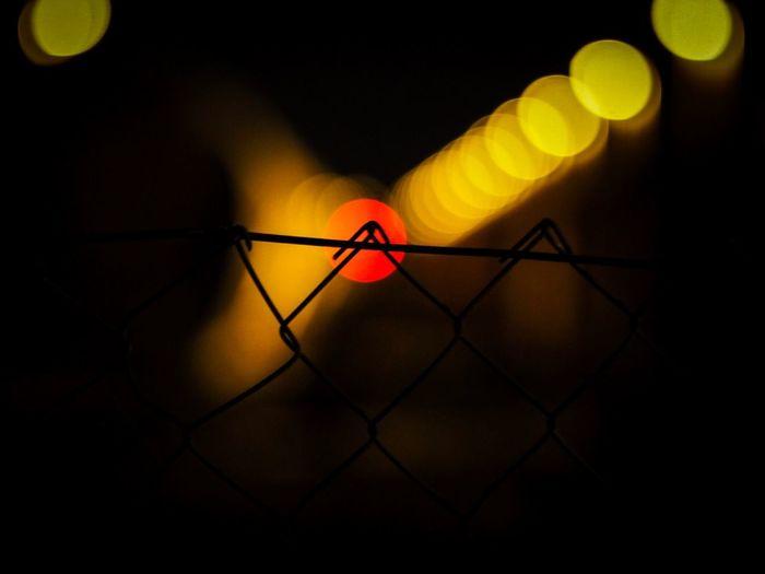 Illuminated Lights Seen Through Chainlink Fence