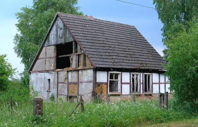 Exterior of abandoned house on field against sky