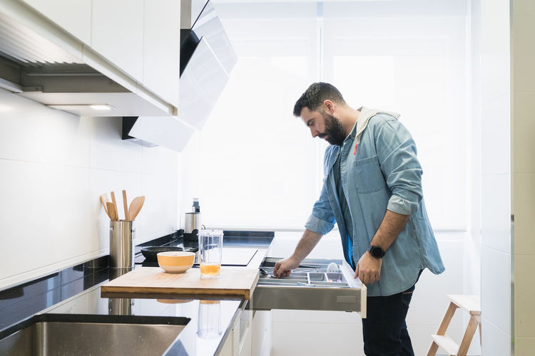 Side view of man standing in kitchen at home