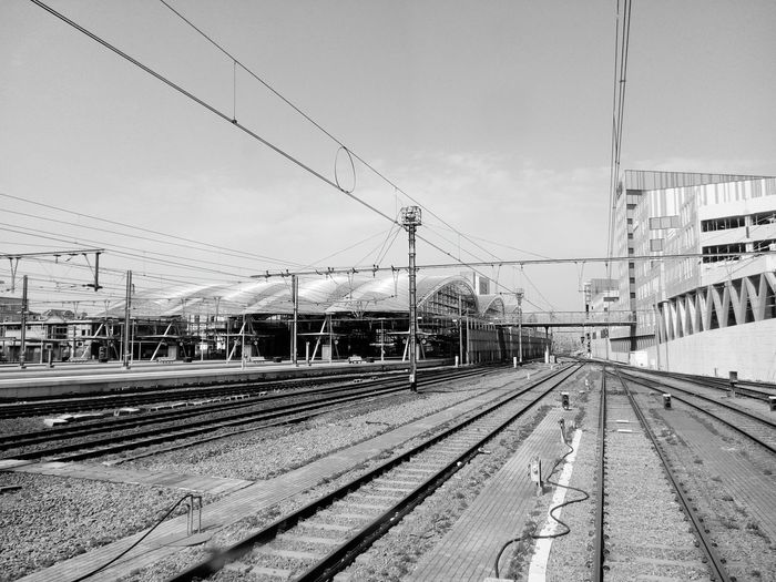 Railroad Tracks At Station In City Against Sky