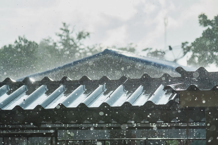 Water drops on roof of building against sky