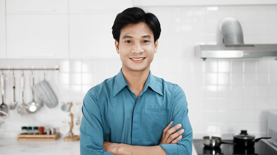 Portrait of smiling young man standing at home