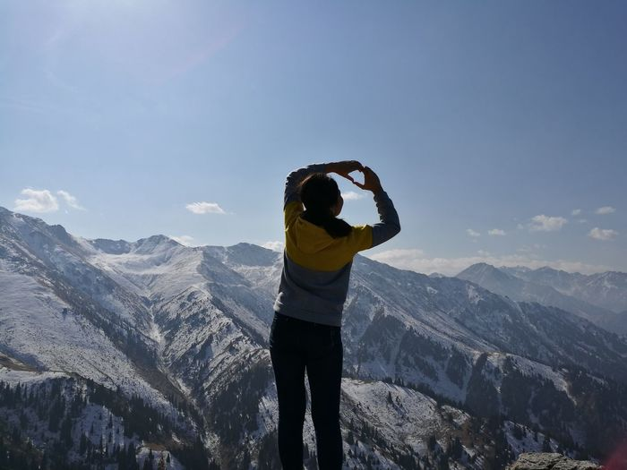Rear view of woman making heart shape while standing on mountain