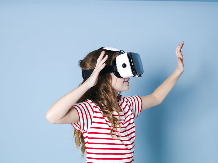 smiling positive girl wearing virtual reality glasses goggles headset, vr box. connection, modern, new generation, concept. girl trying to touch objects in virtual reality, studio shot on blue background Cyberspace Goggles Virtual Glasses Simulation Girl Entertainment Future Generation 360 3D Box Design Business Fun Joyful Gaming Game Electronic Futuristic Blue Copy Space Experience Young Human Woman Model Visual Viewer Video Film Look Observe Learn Pupil School Funny Technology Technical University  Visions Safety Glasses Glass Cool Female One Translated With Www.DeepL.com/Translator Striped Child Indoors  Women Casual Clothing One Person Waist Up Front View Studio Shot Leisure Activity Girls Childhood Blue Background Colored Background Virtual Reality Simulator Lifestyles Hairstyle Teenager Human Arm Obscured Face 3-d Glasses