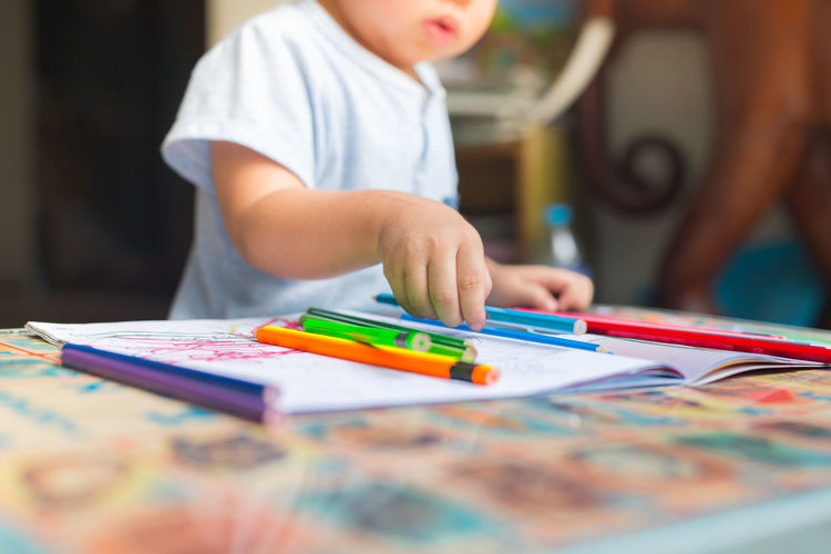 Midsection of boy drawing on table at home