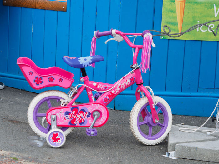 childs bicycle Bicycle Blue Childhood Day Females Land Vehicle Metal Mode Of Transportation Nature Outdoors Pink Color Playground Representation Stationary Text Transportation Tricycle Wheel