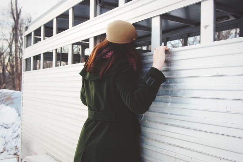 Rear view of woman standing by railing
