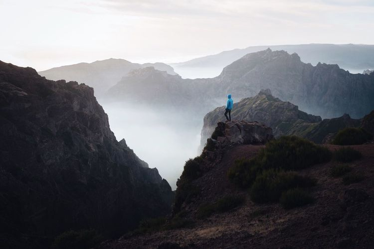 Side view of man standing on mountain against sky