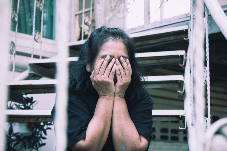 Woman with hands covering face sitting on steps