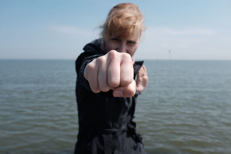 Portrait of young woman fighting stance against sea
