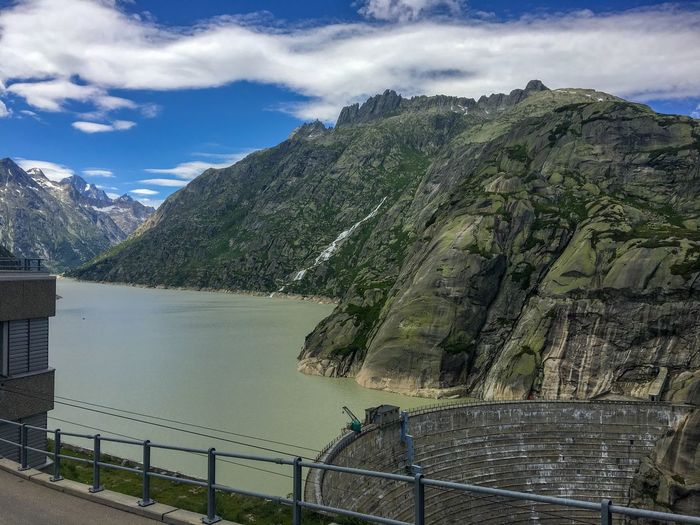Dam in Switzerland 💚 View Mountains And Sky Dam Switzerland Scenics - Nature Green Color Green Blue Sky Water Reservoir Water Resources Lake Reservoir Mountain Water Scenics - Nature Sky Beauty In Nature Cloud - Sky Mountain Range Tranquil Scene Railing Tranquility Day Nature Non-urban Scene Idyllic Architecture Built Structure No People Outdoors
