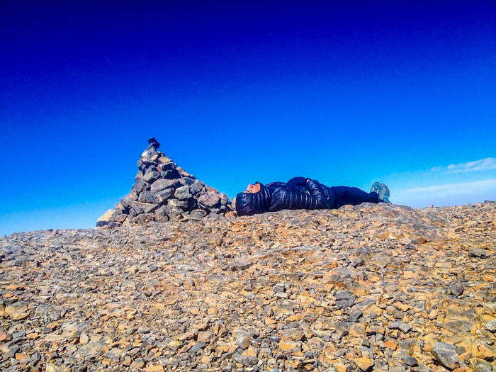 Man sleeping on rock against blue sky