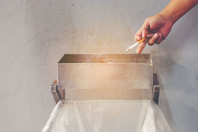 Cropped Image Of Hand Throwing Cigarette In Container