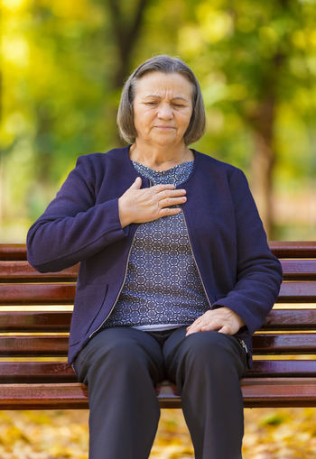 Woman With Hand On Chest Sitting On Bench