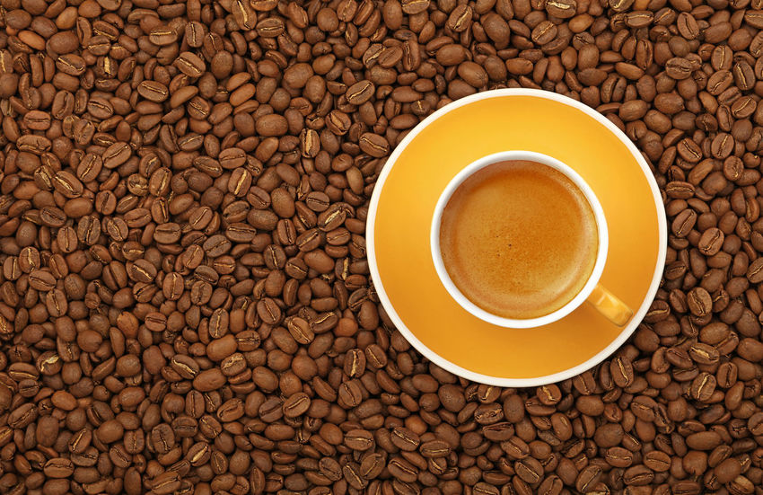 One yellow cup full of espresso coffee on saucer over roasted coffee beans background, close up, elevated top view, directly above Paint The Town Yellow Americano Coffee Time Copy Space Espresso Vivid Close-up Coffee - Drink Coffee Beans Coffee Break Coffee Cup Color Directly Above Drink Food Food And Drink Freshness Frothy Drink Healthy Eating Refreshment Roasted Coffee Bean Top View Yellow