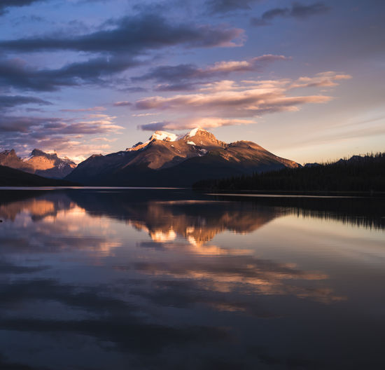 The sun sets over Maligne Lake in Jasper National Park Mountain Reflection Beauty In Nature Sky Scenics - Nature Lake Water Tranquility Tranquil Scene Cloud - Sky Sunset Waterfront Idyllic Mountain Range Nature No People Non-urban Scene Symmetry Snowcapped Mountain Mountain Peak Golden Hour Blue Hour Maligne Lake Jasper National Park Alpine Lake