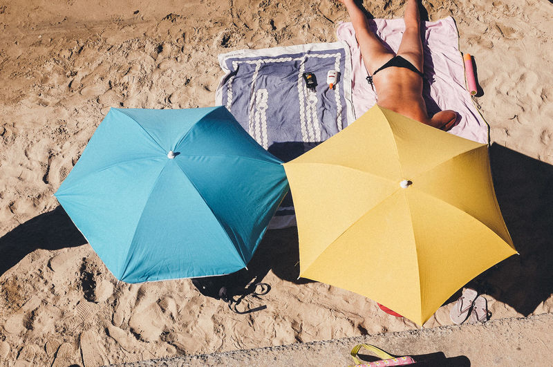 High angle view of woman holding umbrella on beach