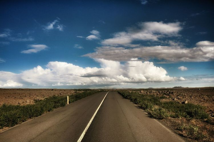 View of country road amidst barren landscape against cloudy sky