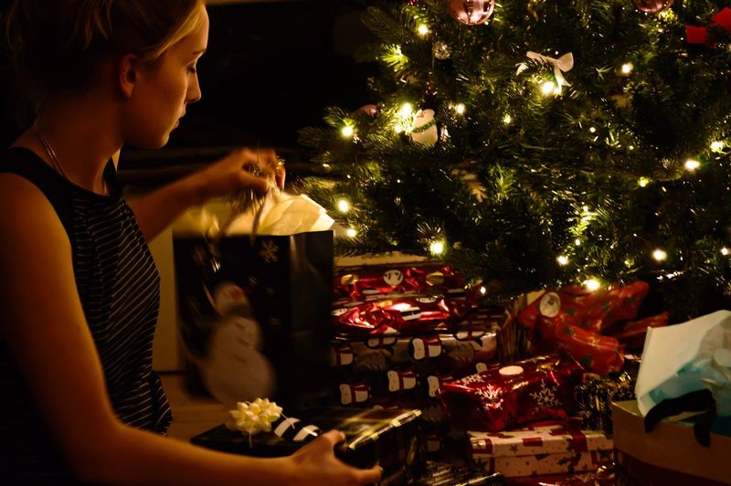 Side view of woman with gifts by illuminated christmas tree at home