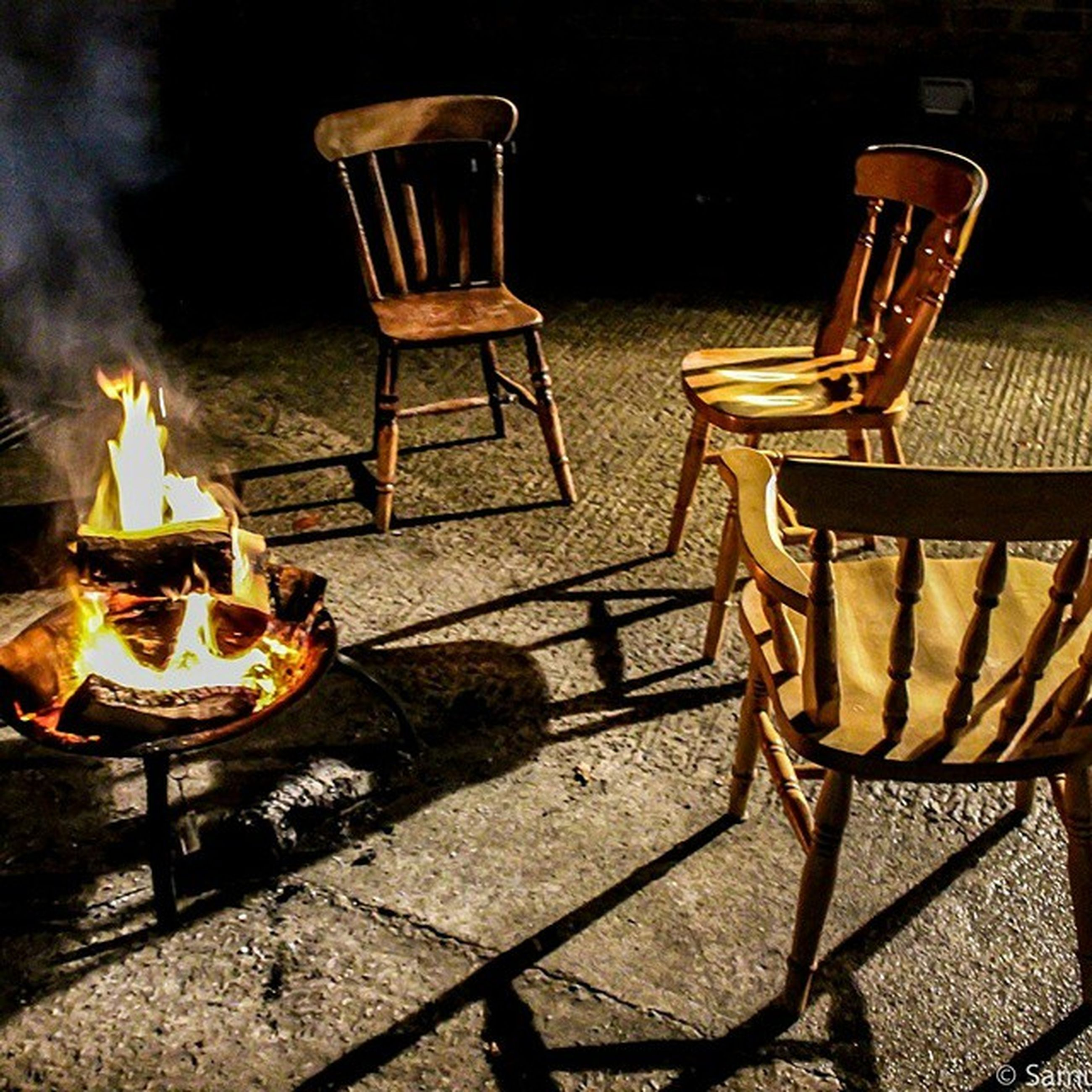 illuminated, night, indoors, fire - natural phenomenon, burning, flame, metal, high angle view, table, heat - temperature, still life, wood - material, chair, no people, food and drink, candle, absence, shadow, metallic