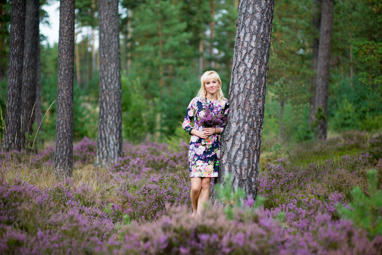Woman standing by tree amidst purple flowering plants in forest
