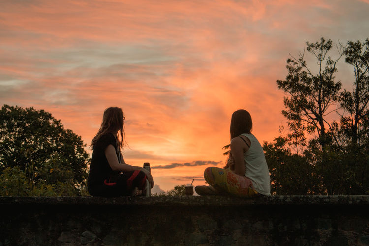 Two young women sitting by trees against sky during orange sunset in a small town
