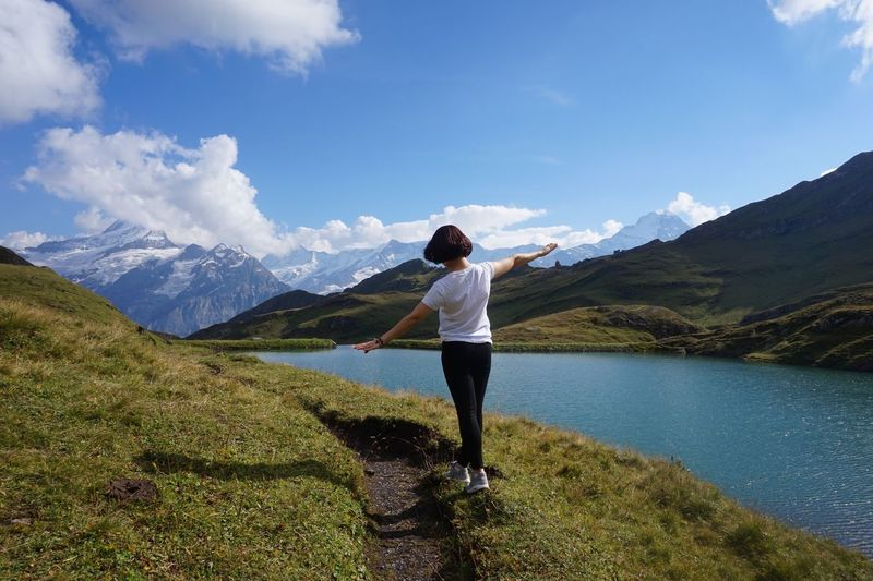 Rear view of woman walking by lake and mountain against sky