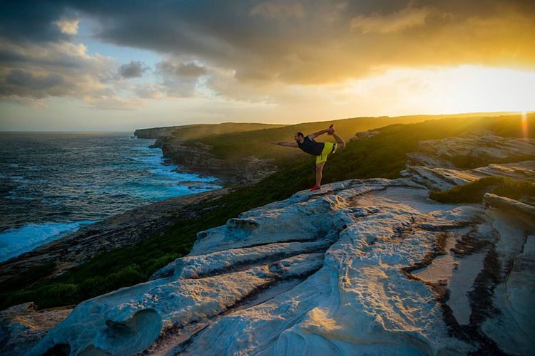 Scenic view of man standing on rocks next to sea