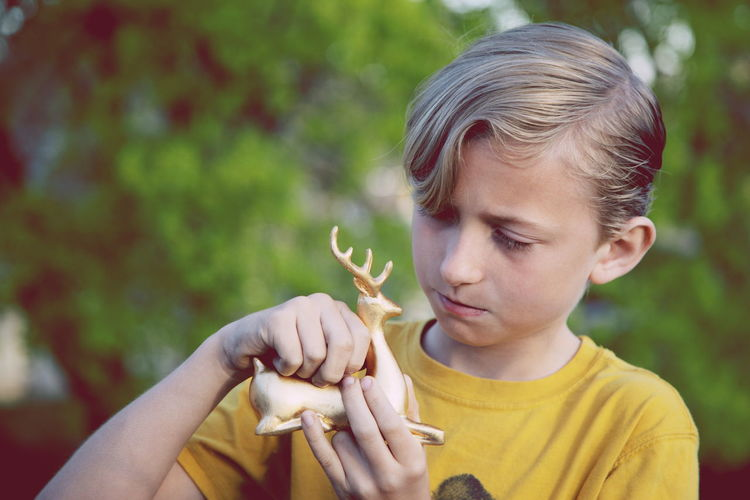 Boy Holding Figurine Deer At Park