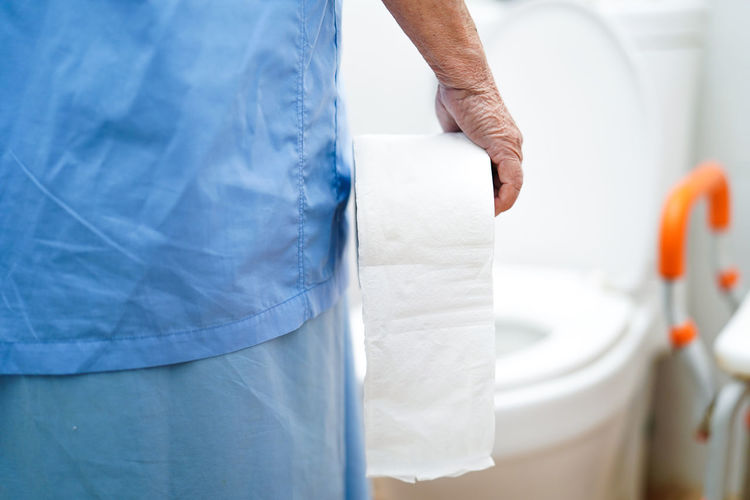 Midsection of female patient holding toilet paper while standing in bathroom