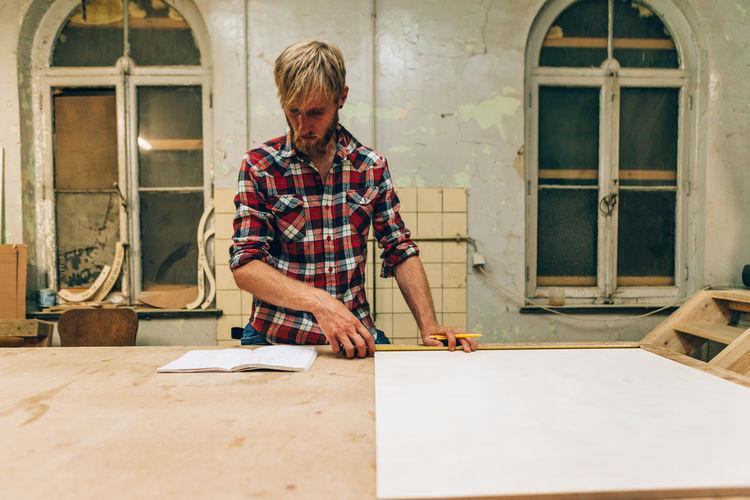 Carpenter measuring plank at workshop