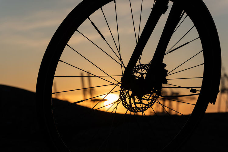 Silhouette of bicycle wheel against sky during sunset