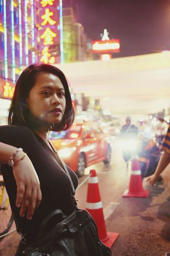 Portrait of woman standing in city at night