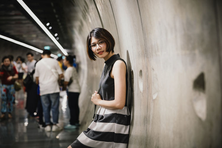 Portrait of asian young short hair beautiful woman wearing glasses and grey dress in tunnel