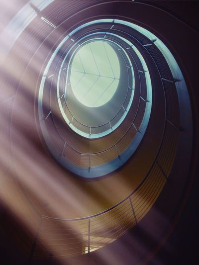 Low Angle View Of Spiral Staircase And Skylight In Building