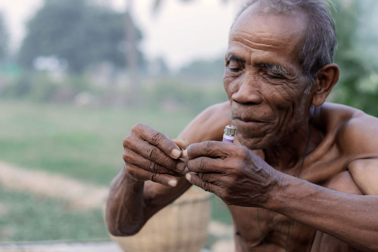 Shirtless Senior Man Holding Cigarette Lighter And Tobacco Product