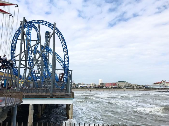 Roller coaster by sea in city against cloudy sky