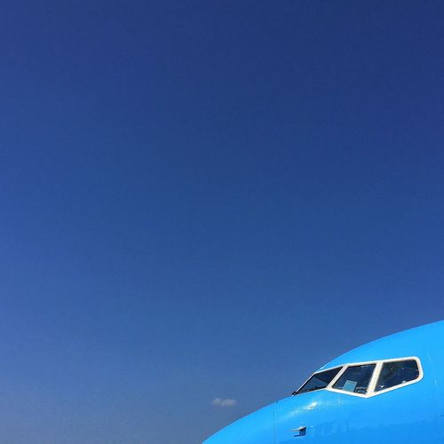 Low angle view of airplane wing against clear blue sky