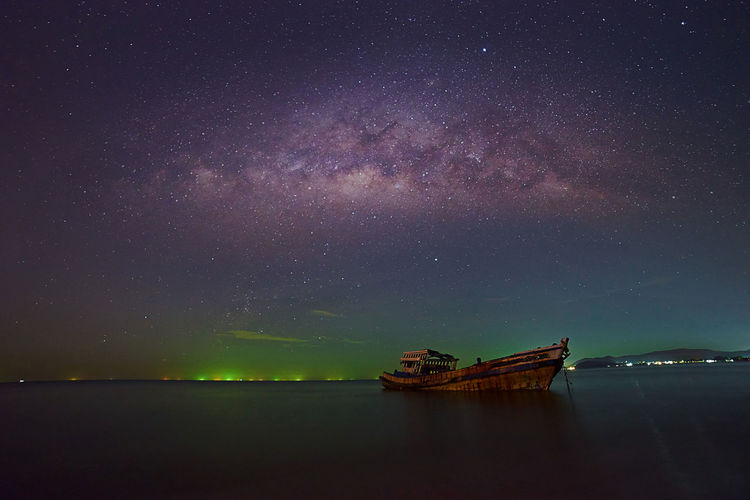 Boat moored against sky at night