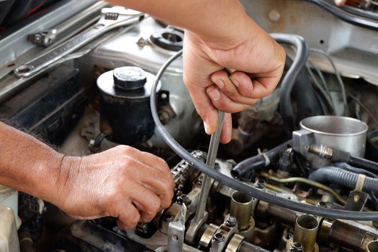 Cropped Hands Of Mechanic Repairing Car Engine