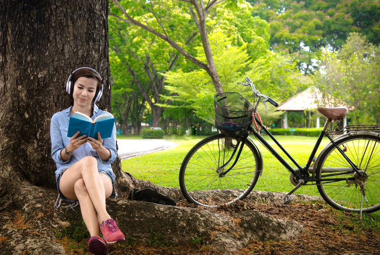 Full length of woman with bicycle sitting on tree trunk in forest