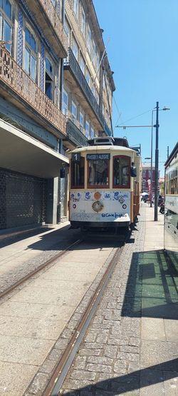 Train on street in city against sky