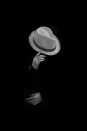 Midsection of woman holding hat against black background