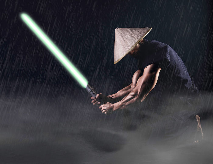 Muscular Man Holding Laser Sword Against Black Background