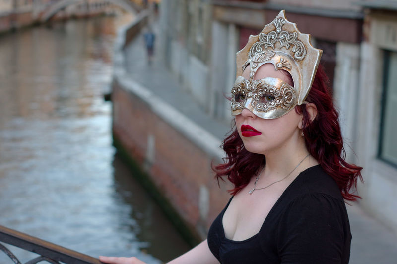 Close-up portrait of woman wearing eye mask against canal