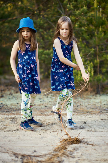 Sisters standing on land