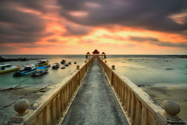A long exposure of a stone jetty leading into the sea during monsun season, Tanjung Balau,Johore,Malaysia Sky Sea Water Cloud - Sky Sunset Horizon Over Water Beach Horizon Land Nature Scenics - Nature Tranquility Tranquil Scene Dramatic Sky Beauty In Nature Direction Architecture Dusk Idyllic No People Outdoors