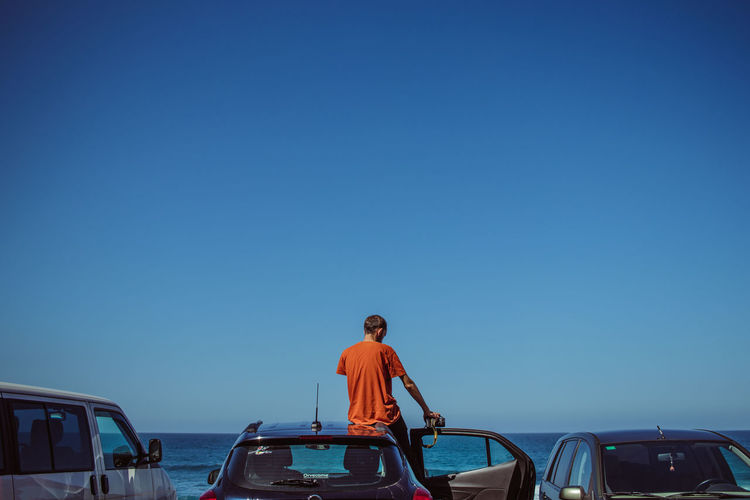 Sky Mode Of Transportation Blue Transportation Clear Sky Copy Space Real People Nature Rear View One Person Nautical Vessel Day Standing Sea Water Men Outdoors Teenager Sunlight