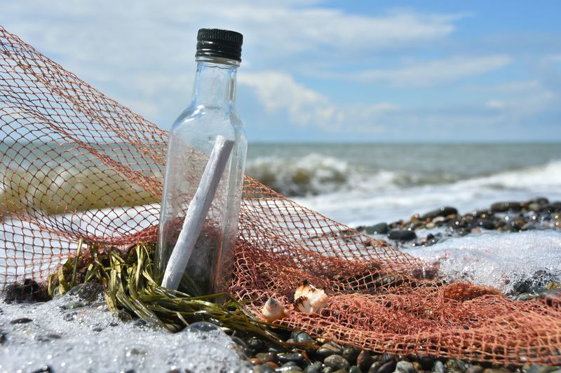 Close-Up Of Message In Bottle By Fishing Net At Beach Against Sky